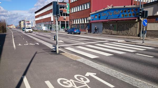 Två körfält för motortrafikanter och stolpe i cykelbanan